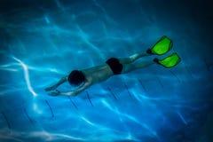 Jongen-zwemmer, deelnemer in onderwaterstrijd - aquatlon, zwemt onder water stock foto's
