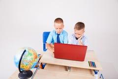 Jongens bij een computer op de Internet-schoollessen stock fotografie