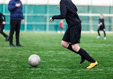 Jongens bij zwarte rode sportkledingslooppas, dribble, aanval op voetbalgebied r Opleiding royalty-vrije stock fotografie