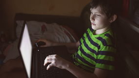 Jongens binnentiener met laptop het spel van computerspelen op Internet stock videobeelden