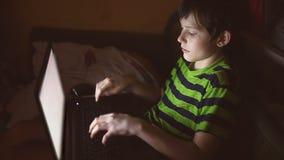 Jongens binnentiener met laptop het spel van de spelencomputer op Internet stock videobeelden