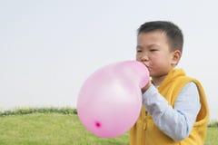 Jongens blazende ballon Stock Afbeeldingen