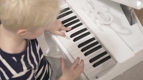 Jongens blonde spelen op de retro piano van de kinderen van witte kleur stock videobeelden