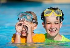 Jongens die in de pool spelen Stock Afbeelding