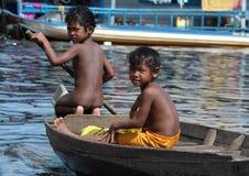 Jongens die door Boot in Tonle-Sapmeer reizen Stock Afbeelding