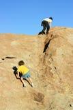 Jongens die op rotsen beklimmen Stock Foto's