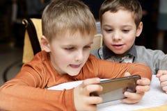 Jongens die in smartphone spelen stock afbeeldingen