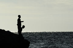 Jongens die van rotsachtige kust vissen stock foto