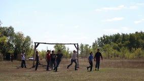 Jongens die voetbal op gebied spelen stock videobeelden