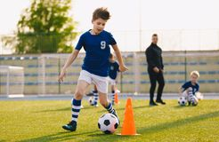 Jongens die voetbal opleiden die op een gebied druppelen Jonge geitjes die de Bal in werking stellen De spelers ontwikkelen voetb royalty-vrije stock foto