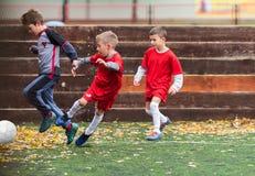 Jongens die voetbal schoppen stock afbeeldingen