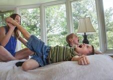 2 jongens die voeten gekieteld krijgen Stock Afbeeldingen