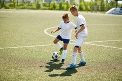 Jongens die voor Bal in Voetbal vechten royalty-vrije stock fotografie