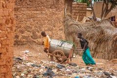 Jongens die water in Afrika verdelen stock afbeeldingen