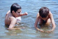 Jongens die in water spelen stock afbeeldingen