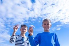 Jongens die Witboekvliegtuig werpen Stock Foto