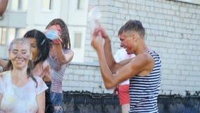 Jongens en meisjes die gebotteld water op mensen gieten - jongerenpret stock videobeelden