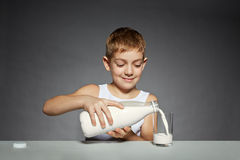 Jongens gietende melk in glas Stock Foto's