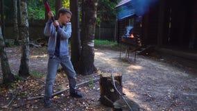 Jongens hakkend hout in de binnenplaats Hij bereidt brandhout voor steadicam schot stock footage