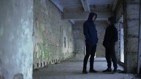 Jongens in hoodie die in de geruïneerde bouw, tienertroep, jonge misdadigers spreken stock footage