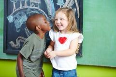 Jongens kussend meisje op wang Stock Afbeelding