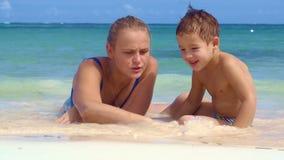 Jongens lettende op moeder die op zand trekken stock video