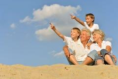 Jongens met grootouders die op zand zitten Stock Fotografie