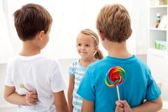 Jongens met lollys en een meisje Stock Fotografie
