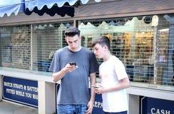 Jongens met Telefoons in de Straat stock fotografie