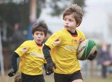 Jongens, onder het 8 verouderde, gele rugby van het jasjespel Stock Foto's