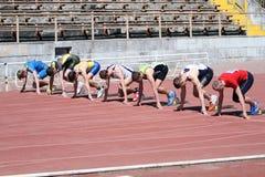 Jongens op het begin van de 100 meters ras Stock Foto