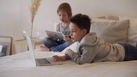 Jongens in ouders` bed bij ochtend met laptop en tablet De broers spelen computerspelen Siblings en gadgets stock videobeelden