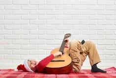 Jongens speelmuziek op gitaar, gekleed in een rode wollen sweater en santahoed, die op een rode geruite algemene, witte bakstenen Stock Afbeeldingen