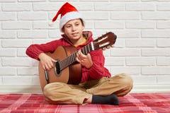 Jongens speelmuziek op gitaar, gekleed in een rode wollen sweater en santahoed, die op een rode geruite algemene, witte bakstenen Stock Foto's