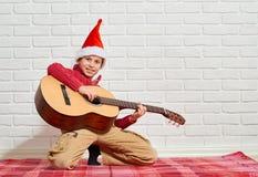 Jongens speelmuziek op gitaar, gekleed in een rode wollen sweater en santahoed, die op een rode geruite algemene, witte bakstenen Stock Afbeelding