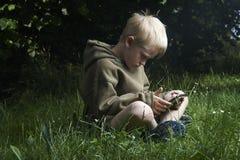 Jongens speelspel met tabletpc in openlucht Royalty-vrije Stock Afbeeldingen