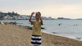 Jongens videopraatjes op smartphone op het strand in de avond Het gebruiken van een draagbaar handbediend apparaat op de zomervak royalty-vrije stock foto's
