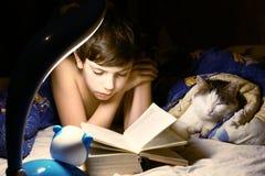 Jongensavond gelezen boek met kat Stock Afbeelding