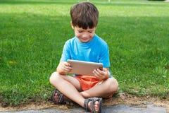 Jongensglimlach met tablet openlucht Stock Fotografie