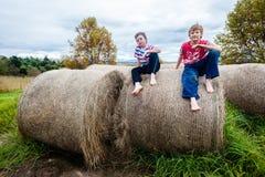 Jongensjonge geitjes die het Landbouwbedrijf van Grasbalen zitten Stock Foto