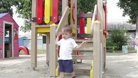 Jongenskind onderaan de treden op de speelplaats stock footage