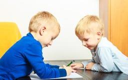 Jongenskinderen die met pen doend thuiswerk schrijven Gedetailleerde mening van haar wapen Royalty-vrije Stock Foto's