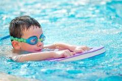 Jongenspraktijk het zwemmen stock afbeelding