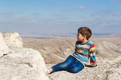 Jongensrust op de rotsen over de vallei Royalty-vrije Stock Afbeeldingen