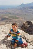 Jongensrust op de rotsen over de vallei Royalty-vrije Stock Afbeelding