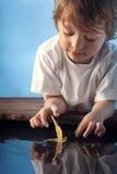Jongensspel met bladschip in water royalty-vrije stock foto