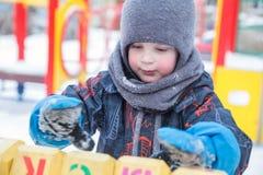 Jongensspelen in de speelplaats in de winter Royalty-vrije Stock Foto's