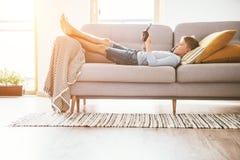 Jongensspelen met elektronische apparaten - gamepad verbonden aan smartphone die op de comfortabele bank in de huiswoonkamer ligg royalty-vrije stock foto