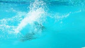 Jongenssprongen in het water met een draai stock video