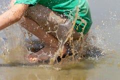 Jongenssprongen in knoeiboel vuil water stock afbeeldingen